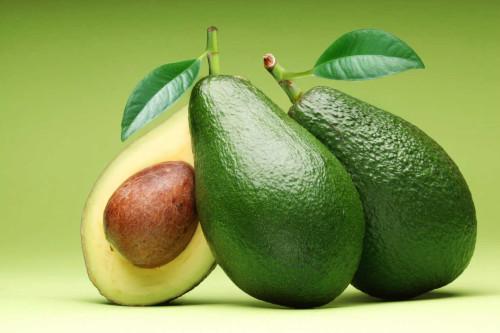 3 авокадо на салатовом фоне