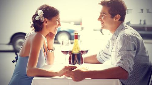 Девушка и парень сидят в ресторане и держатся за руки