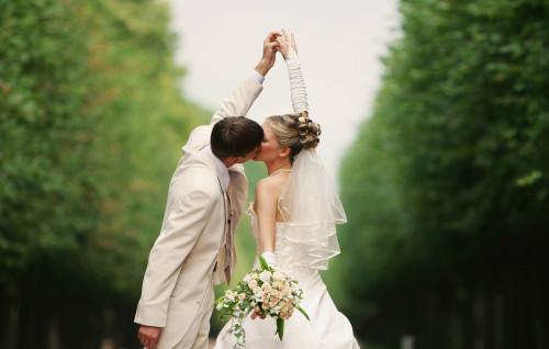 Жених и невеста целуются в парке