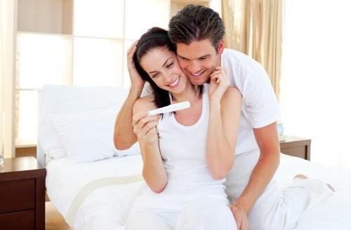 Мужчина и женщина смотрят на тест по которому определяют беременность
