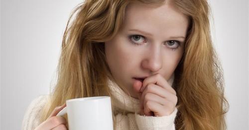Красивая девушка кашляет держа чашку в руке