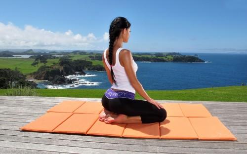 Девушка медитирует сидя на горе