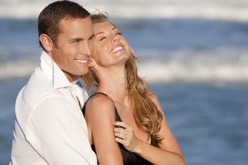 Парень обнимает девушку на фоне моря