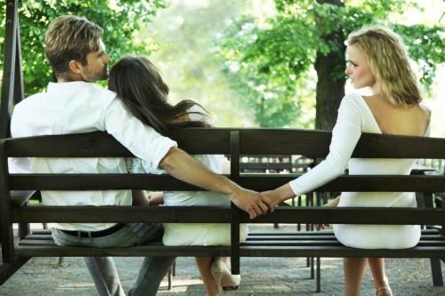 Парень, его жена и любовница сидят на скамейке, парень обнимает жену и держит за руку любовницу