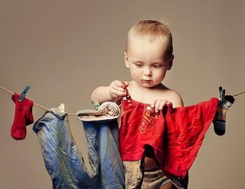 Маленький мальчик вешает бельё на верёвку