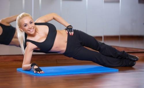 Красивая девушка делает упражнение для боков